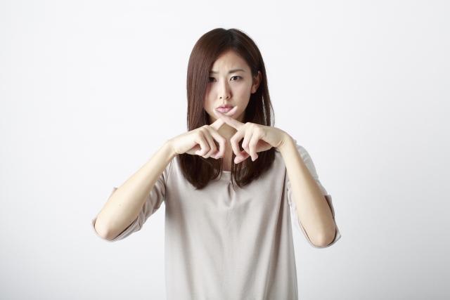 女性が指でバツ印を作っている