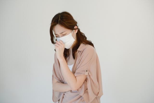 マスクをして咳き込む女性