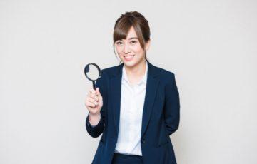 虫眼鏡を持つ女性社員